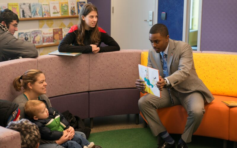 college student reads book to children