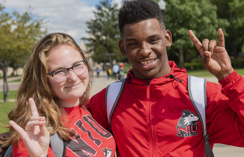 two NIU students outside on campus making the huskie hand sign