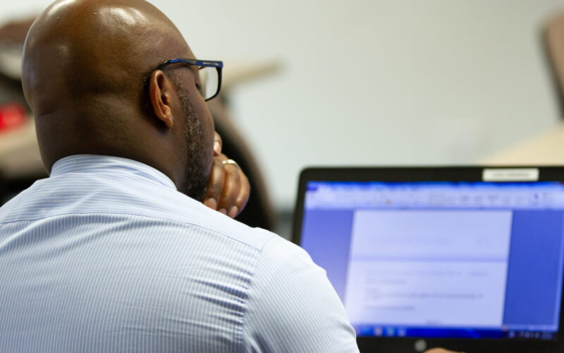 Back of man sitting in front of computer
