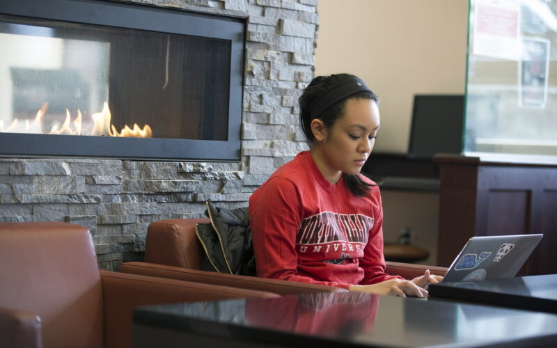 female student using laptop in front of fireplace in student center
