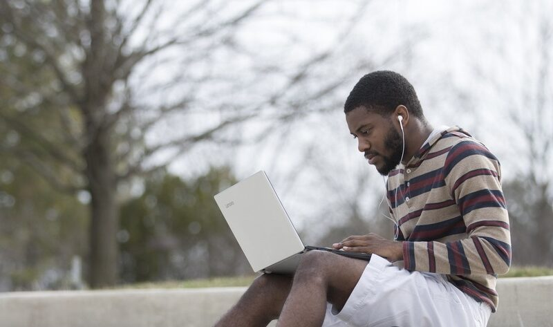 man sitting outside on steps wearing earbuds and typing on laptop