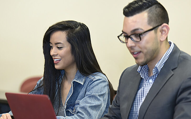 female and male student working on laptops