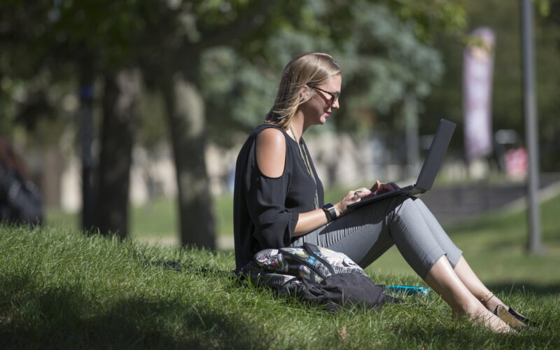 woman sitting in grass working on laptop