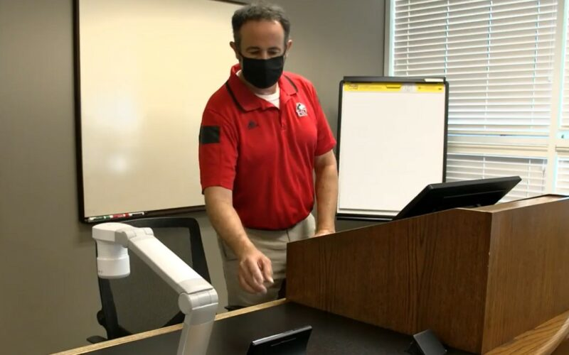 man wearing a face mask setting setting up classroom instructor station