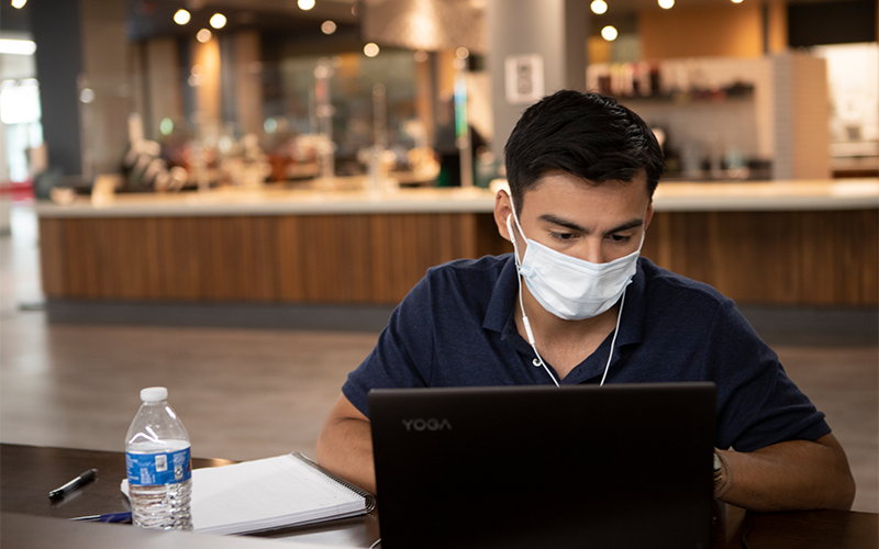 student wearing mask typing on laptop