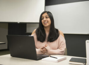 female student smiling in front of computer