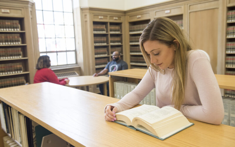 female student studying a book in the law library with two students talking in the background