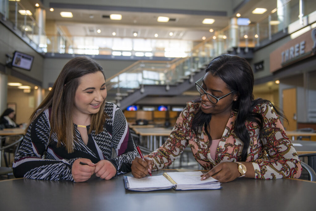 two students looking at notebook in barsema atrium