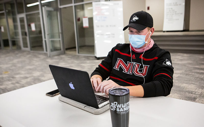 student wearing mask working on laptop