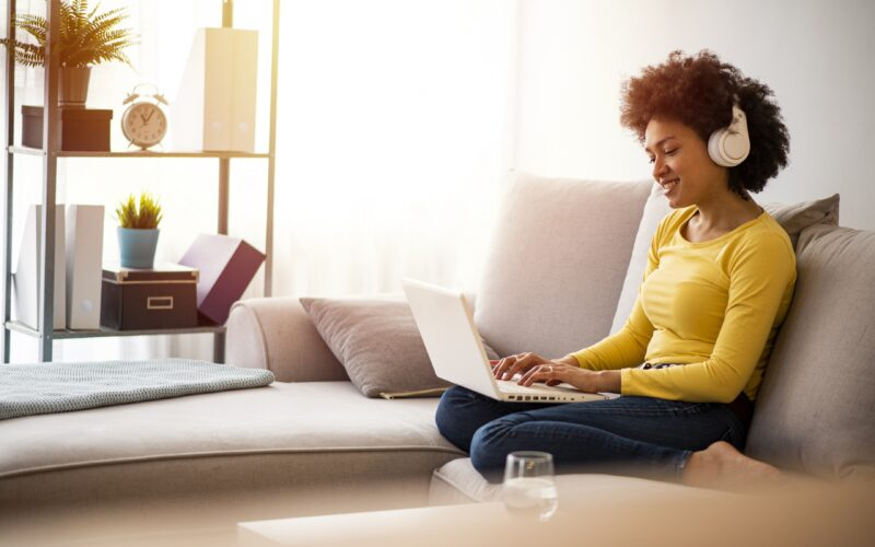 Young modern woman having Video Conference at home. Young modern woman working from home, using laptop in quarantine. Young modern woman using lap top at comfort home