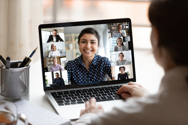 Woman sits at desk looking at computer screen where collage of diverse people use videoconferencing app