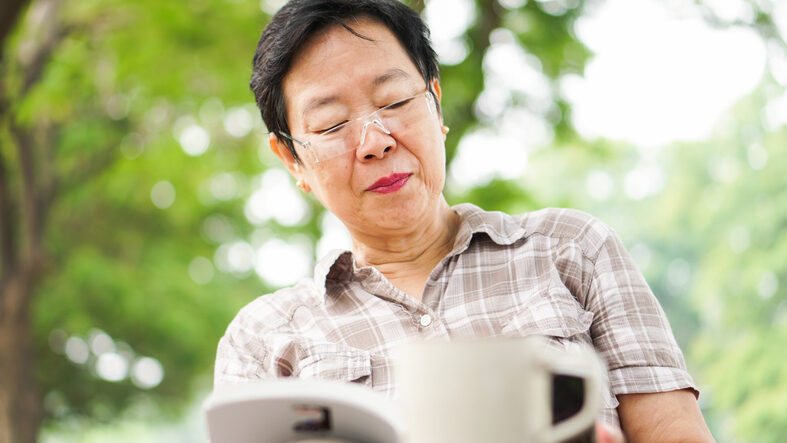 Asian senior woman reading book drinking coffee in sunny park