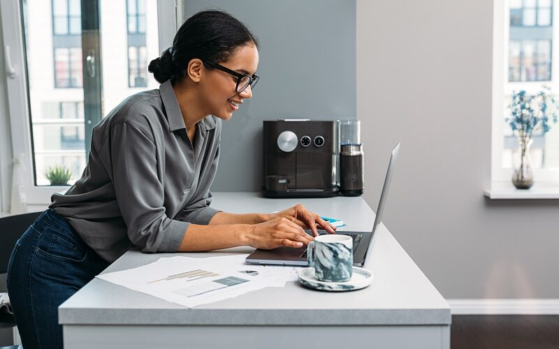 Side view of smiling woman working with laptop on kitchen counter at home
